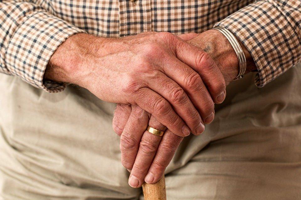 Un homme sénior avec une canne en bois